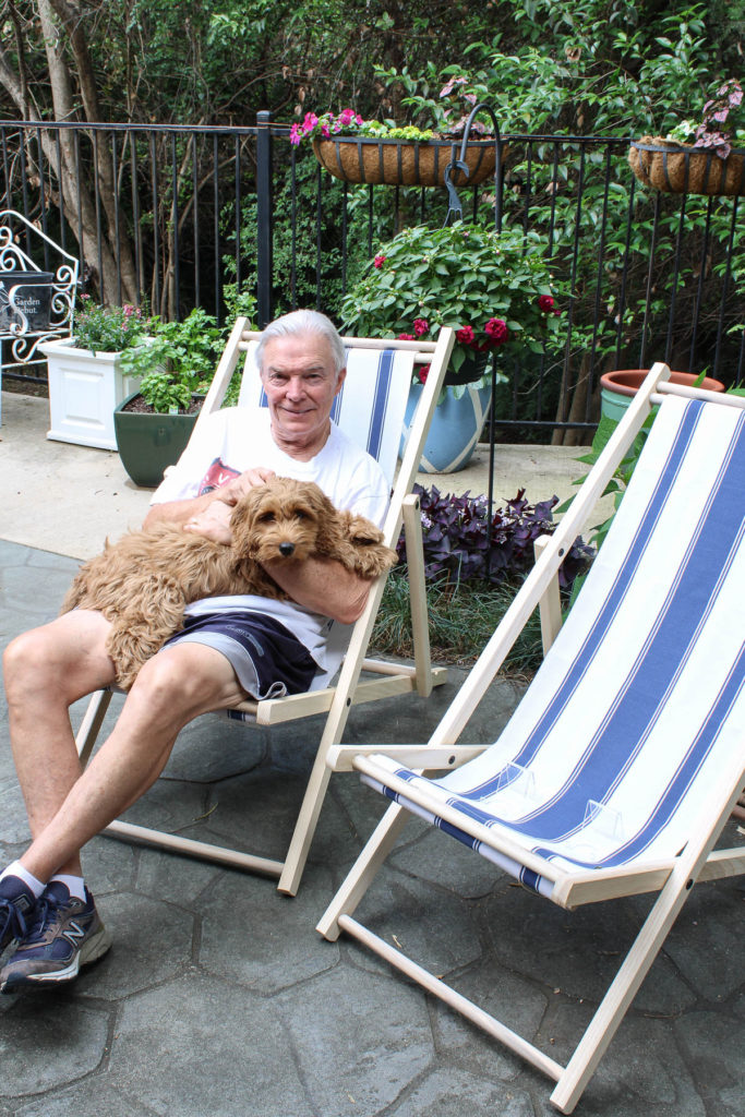 man in cabana chair with dog