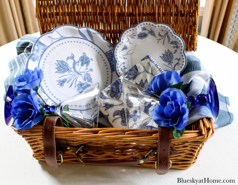blue plates and napkins in wicker picnic basket