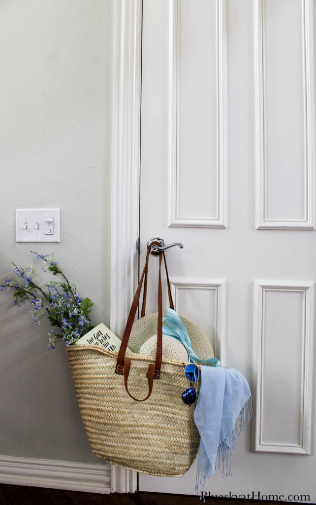 woven French market tote hanging on door knob