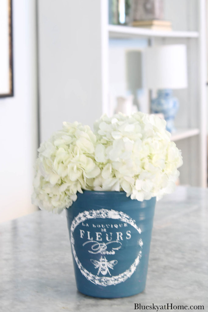 painted blue ceramic flower pot with white hydrangeas on counter