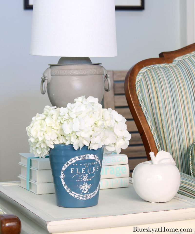 painted blue ceramic flower pot with white hydrangeas on table