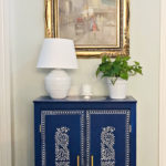 blue cabinet with white lamp and plant