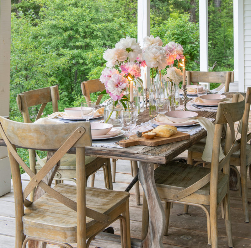 table setting pink peonies in glass bottles