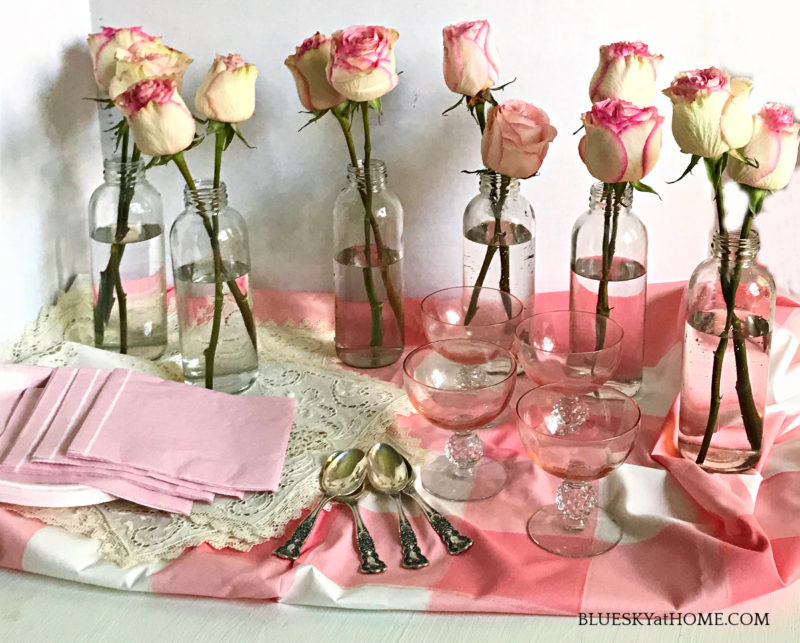 pink roses in bottles, pnk check tablecloth, pink plates, silverware, pink napkins