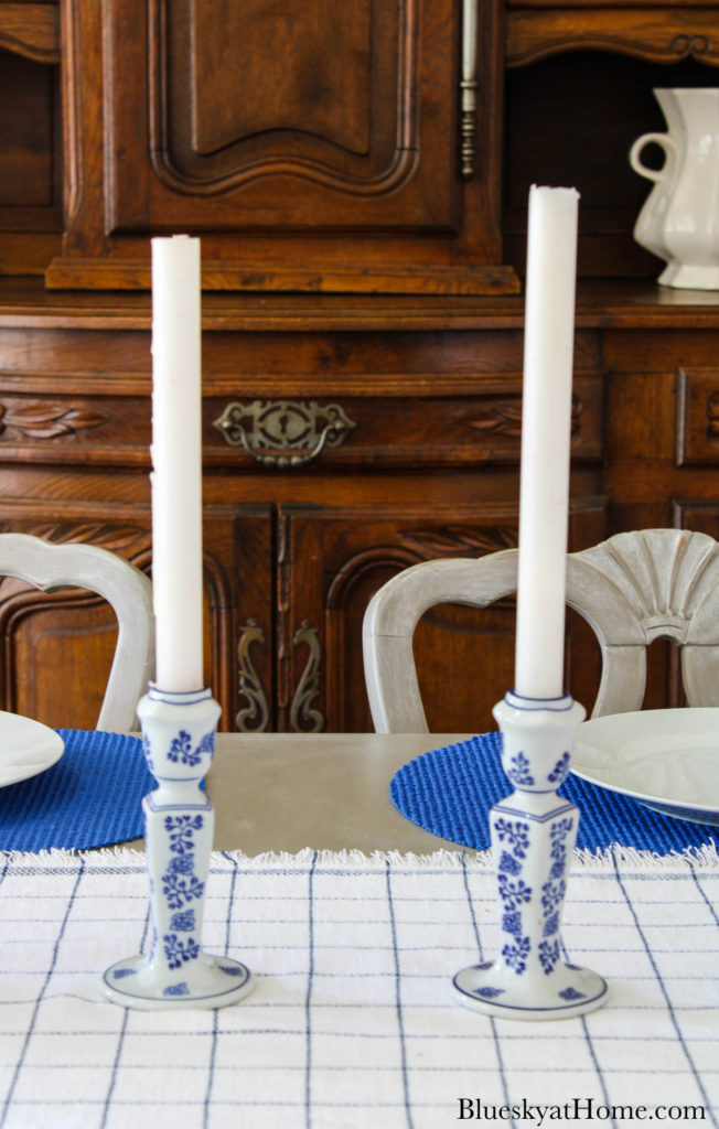 white candles in blue and white candlesticks