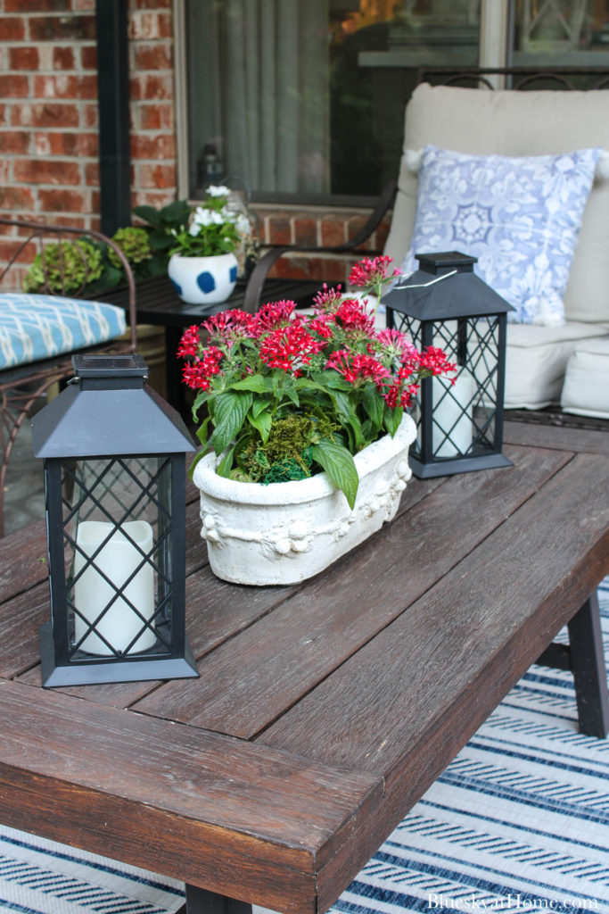 wood and metal patio table with flowers and black lanterns