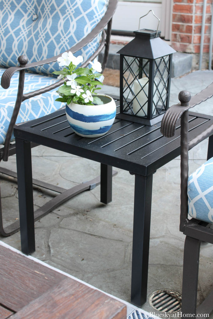 black metal patio table with pot of flowers