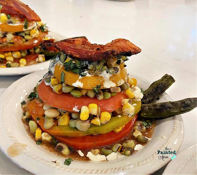 stack of tomatoes with corn, okra, peas, and bacon