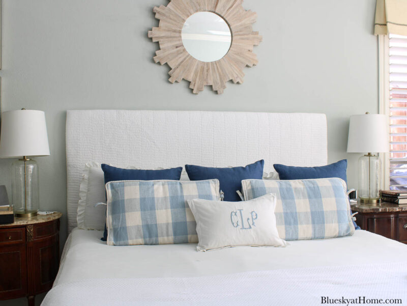 kind bed with white fabric headboard and blue pillows