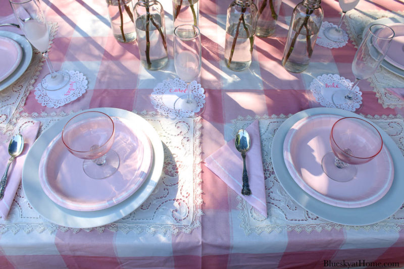 pink roses in bottles on pink table setting