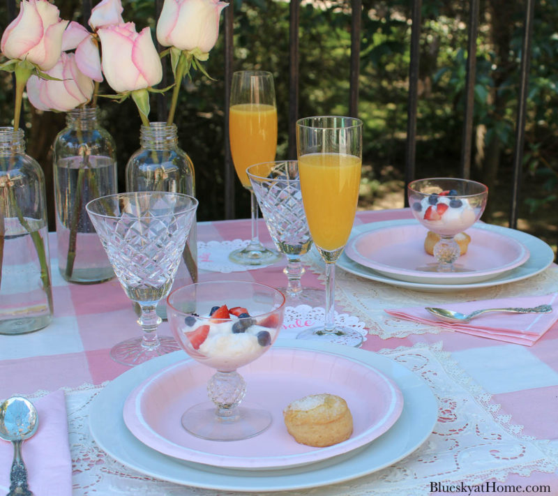 pink table with bowl with yogurt and strawberries and blueberries