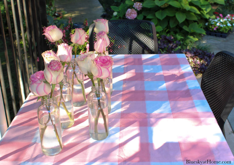 pink and white table cloth with pink roses in bottles
