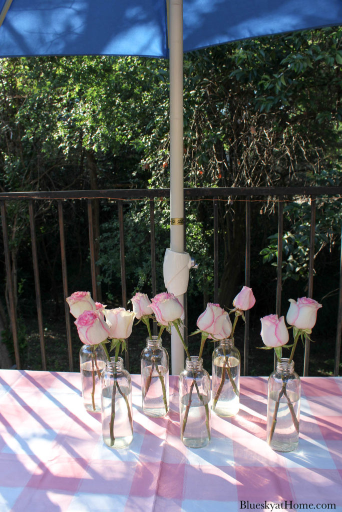 pink check tablecloth with pink roses in glass bottles