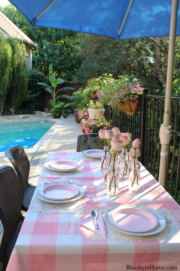 pink check tablecloth with pink roses in glass bottles and pink plates