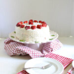 girl putting mint leaf on strawberry vanilla cake with one plate