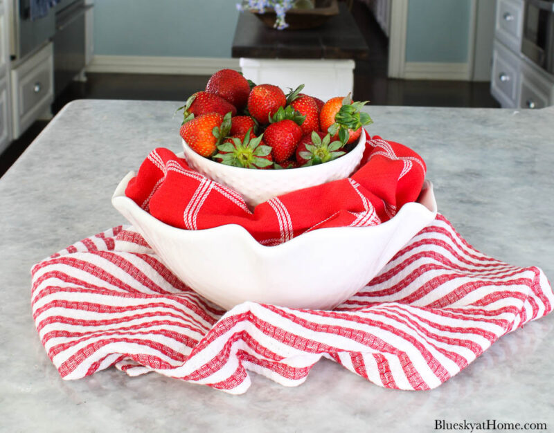 strawberries in white bowl with red check towel