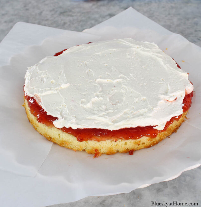 vanilla icing and strawberry preserves on cake layer