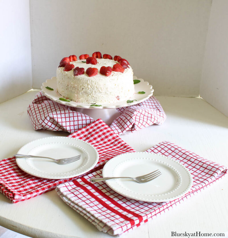 strawberry vanilla cake on pink cake stand with two plates