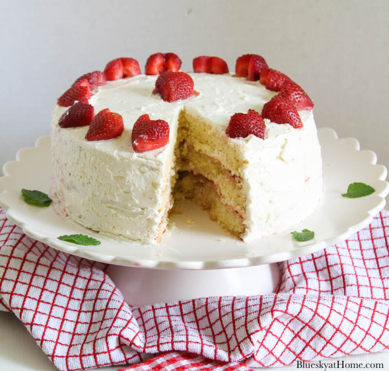 strawberry vanilla cake on pink cake stand with slice cut out