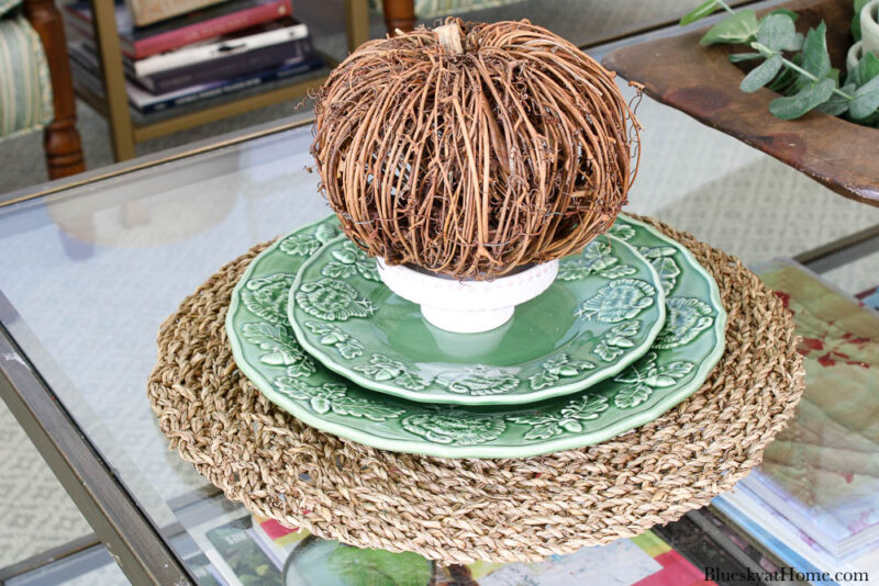 twig pumpkin on white stand and green plates