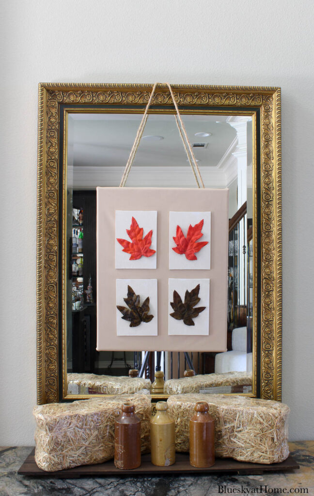 4 fall leaf canvases on large canvas hanging on mirror