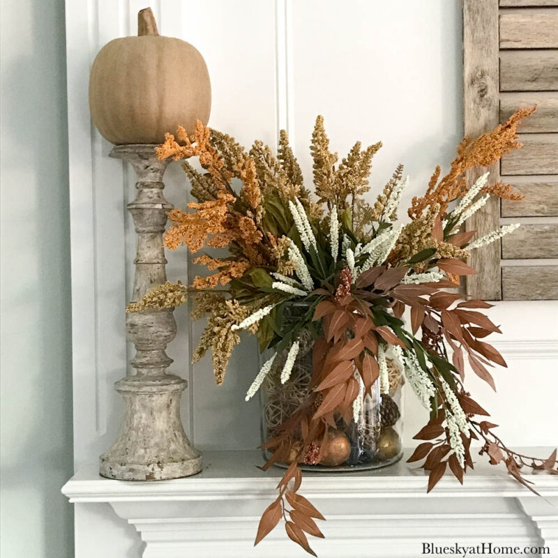 neutral pumpkin on candlestick with flal florals in glass jar on fall mantel