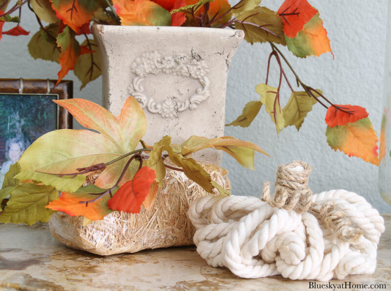 white rope pumpkin, small hay bale, adn stone vase with orange faux florals.