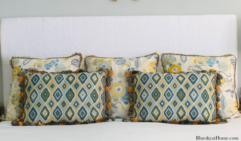 blue and gold pillow shams on bed