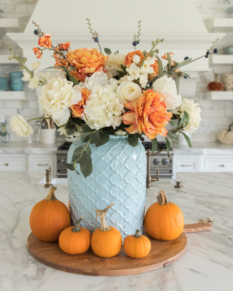 light blue vase with white and orange flowers and pumpkins
