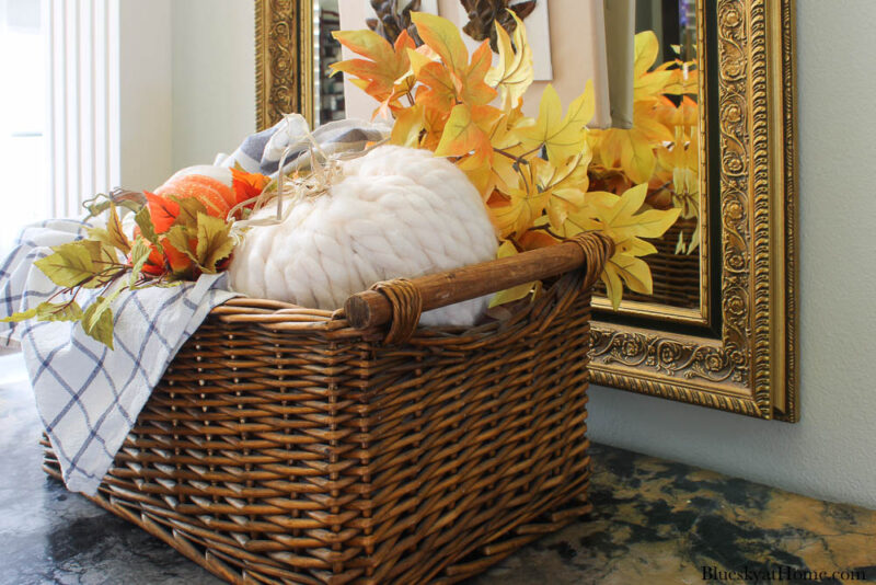decorative pumpkin with yarn in basket with blue check dishtowels