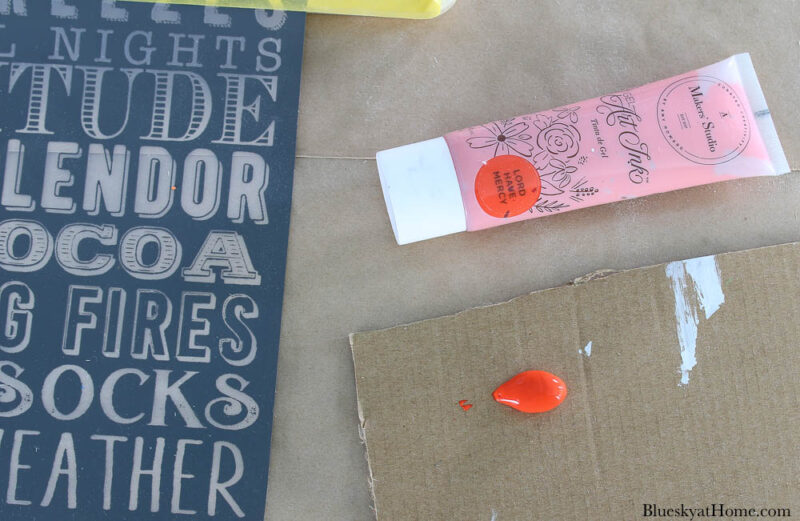 orange paint in tube and on cardboard