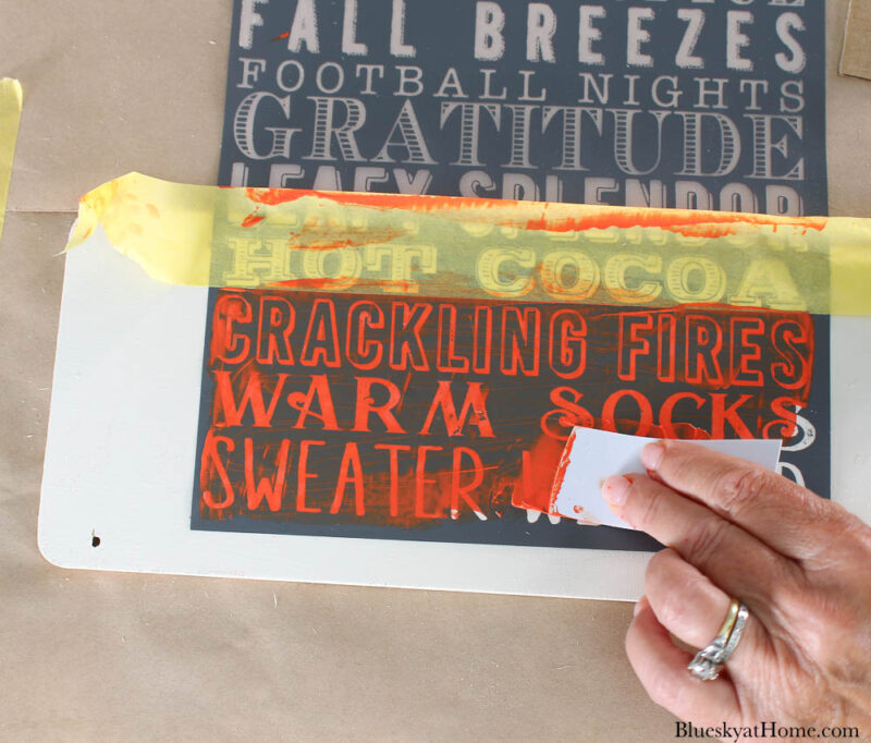 stenciling wood sign with orange paint