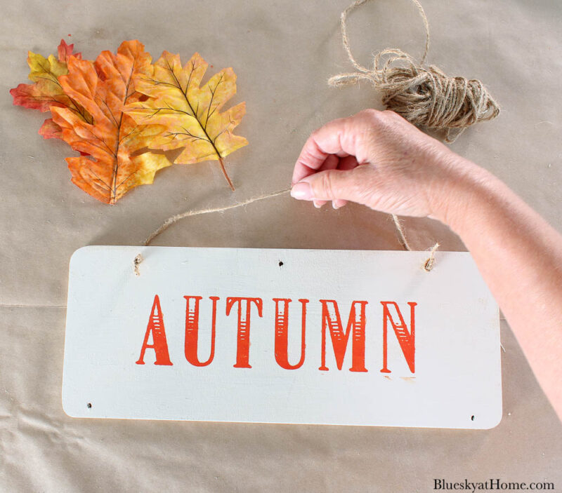 wood sign with word autumn and leaves