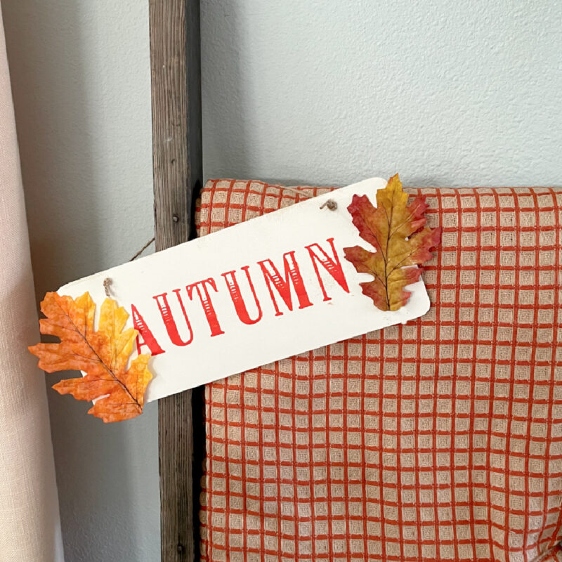 orange throw on vintage ladder and wood sign that says autumn