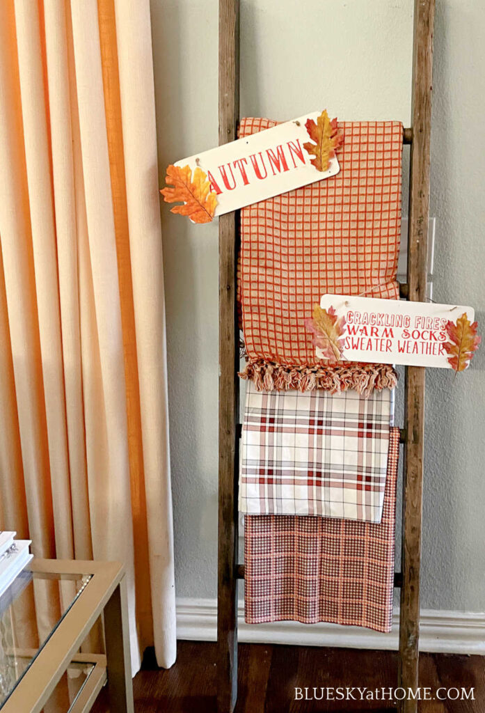 fall colored throws on vintage ladder and wood signs